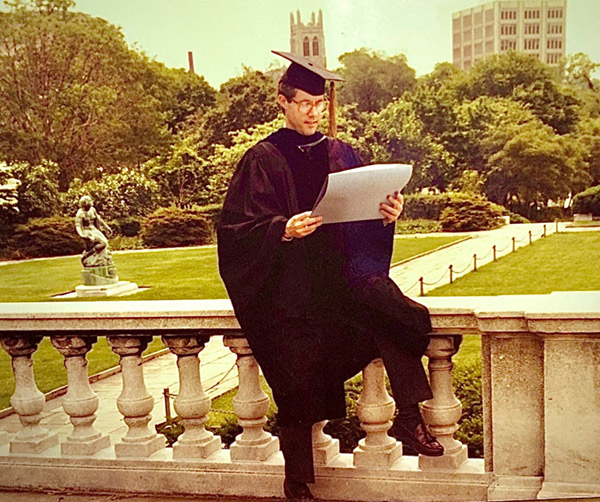 Doug sitting on railing in graduation robes